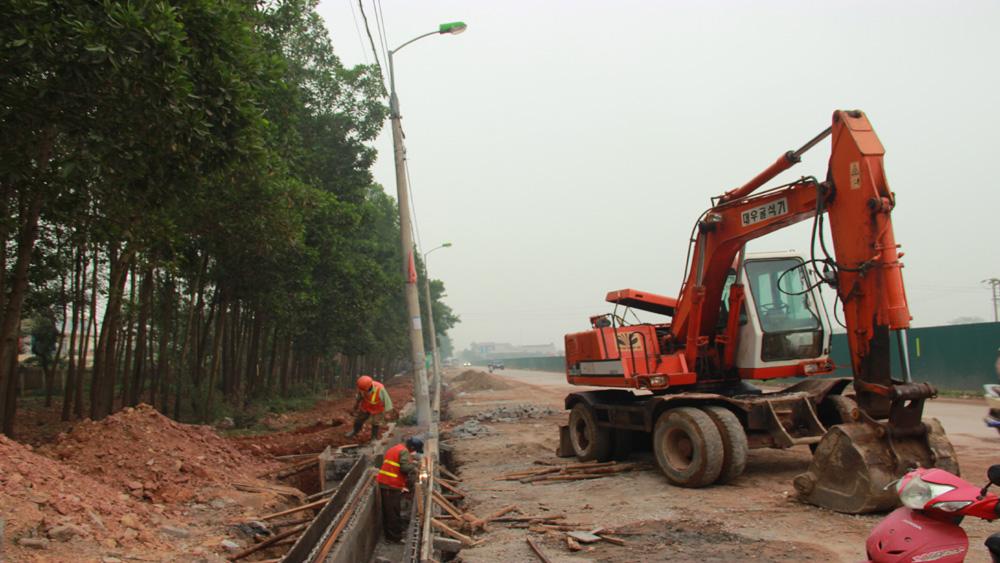 Hàng chục cột đèn chiếu sáng chưa được di dời khiến việc thi công cải tạo, nâng cấp đường tỉnh 292 gặp nhiều khó khăn.